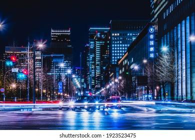 HIBIYA, TOKYO, JAPAN - February 15, 2021 : Night view of Buildings in Marunouchi, Chiyoda District, Tokyo. Imperial Palace, Hibiya moat and Hibiya Street.
