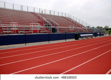 hich school red track in front of red and blue bleachers