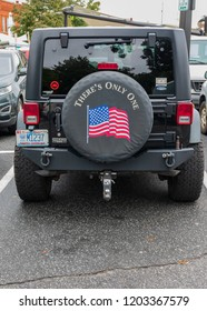 """HICKORY, NC, USA-10/14/18: The rear spare tire cover on a Jeep has image of us flag and the words """"There's only one""""."""