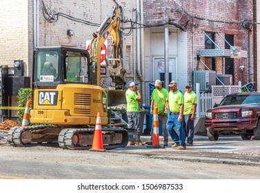 HICKORY, NC, USA-13 SEPT 2019: Road workers and Caterpillar (CAT 305E) on city street.