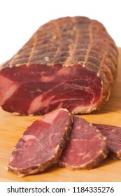 Hickory smoked sliced beef shoulder stuffed in a net isolated on white background - Dimljeni suvi govedji vrat