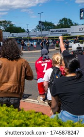 HICKSVILLE, NY / USA - MAY 31 2020: A protester in a Colin Kaepernick hoodie takes a knee along S Oyster Bay Rd opposing police brutality and racism after the death of George Floyd in Minneapolis.