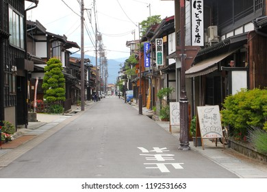 HIDA FURUKAWA, JAPAN - June 5, 2018. People are walking and cars parked in old town street with wooden houses from Edo period, green trees, billboards and mountain view. Gifu prefecture.
