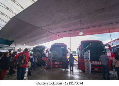 Hidalgo, Mexico - June 24, 2018: Bus terminal in Pachuca with passengers waiting to board and a row of trucks parked on their platforms