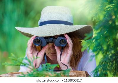 hidden between bushes, a woman secretly observes with binoculars
