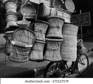 Hidden cyclist in Delhi riding a bike dangerously on road overloaded with wicker baskets