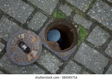 Hidden geo cache in street well