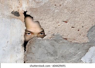 A hidden man spying through a broken concrete wall.