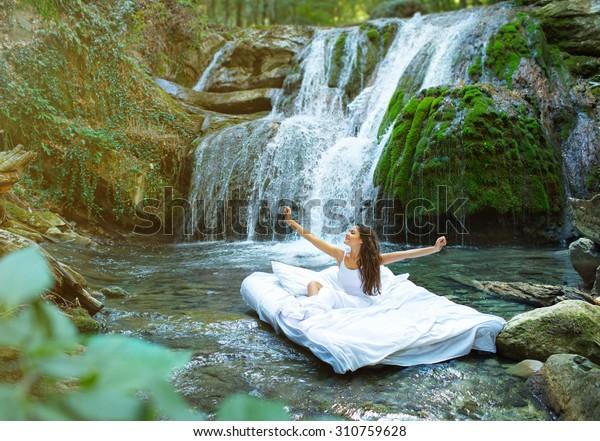 Скрытое место. Спящая женщина в глубоком лесу лежит на воздушной подушке. Водопад на спине