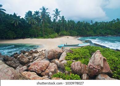 Hidden secret lonely paradise beach with boat on the shore at Mirissa, Sri Lanka