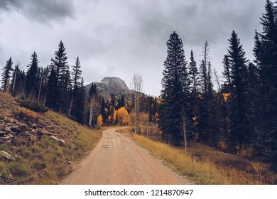 Hidden snow-covered peaks in southwest Colorado in fall colors and ominous clouds