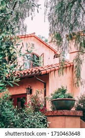 Hidden Spanish style home along the streets of Ojai California. Terra cotta shingles and hand painted tiles show character. Lush plants give a secret garden feel to the welcoming home.
