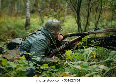 Hidden unidentified re-enactor dressed as german wehrmacht soldier sitting with rifle in an ambush in forest.