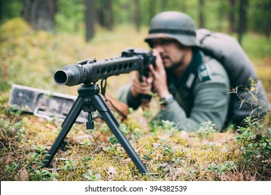 Hidden unidentified re-enactor dressed as german wehrmacht soldier aiming a machine gun at enemy from trench in forest