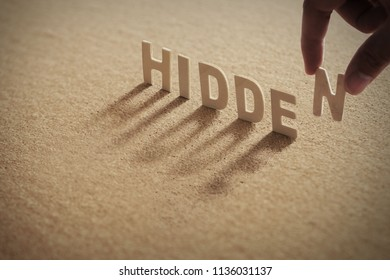 HIDDEN wood word on compressed or corkboard with human's finger at N letter.