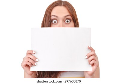 Hide and seek. Amazed red-haired woman covering her face with paper board on white isolated background.