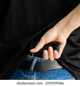 Hided handgun under the denim belt. a man in jeans and a t-shirt holds a gun in his hand from the back