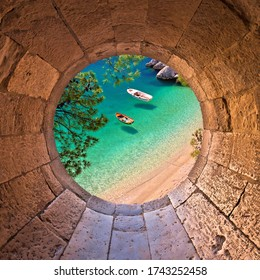 Hiden beach in Brela with boats on emerald sea aerial view through stone window, Makarska riviera of Dalmatia, Croatia