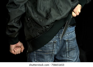 hides a big  knife behind his back in young man hand of a  black jacket and jeans clenched fist. Defend Against a Knife Attack concept close up, selective focus , blurred dark background