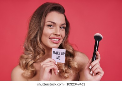 Hiding all imperfections.  Beautiful young woman smiling and applying make-up brush while standing against pink background