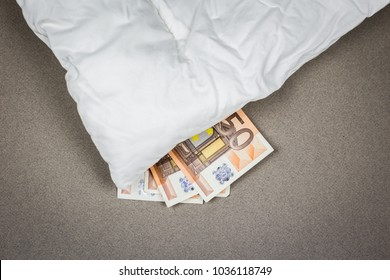 Hiding money under the pillow. 50 euro bank notes under the white pillow.