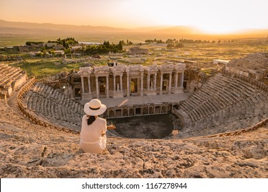 Hierapolis ancient city Pamukkale Turkey, young woman with hat watching sunset by the ruins Unesco