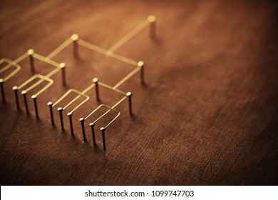 Hierarchy, command chain, company / organization structure or layer and grouping concept image. Top down structure made from gold wires and nails on rustic wooden surface. Shallow depth of field.