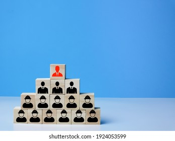 Hierarchy and leadership concept. A bunch of wooden blocks with people icons isolated on blue background.
