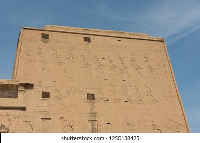 Hieroglypic carvings on wall at the entrance to ancient egyptian temple of Horus in Edfu
