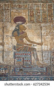 Hieroglypic colourful carving paintings on wall at the ancient egyptian temple of Khnum in Esna with god Sekhmet