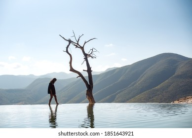 Hierve El Agua, Oaxaca / Mexico - 01/04/2019: Female tourist walking on the edge of the fresh water springs in Hierve El Agua with beautiful mountains and ominous tree in the background