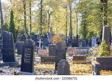 HIETANIEMI CEMETARY, HELSINKI, OCTOBER 18, 2014. . Tombstones in Hietaniemi cemetary, in Helsinki on October 18th, 2014. Trees with green and yellow leaves in the autumn.