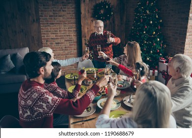 High above angle view of merry noel friends family gathering. Cheerful grey-haired grandparent saying toast, grandchildren brother sister, daughter, son sit around table, fun joy house feast, congrats