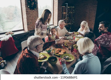 High above angle view of noel family gathering, meeting. Cheerful grey-haired grandparents, grandchildren, daughter, son, brother, sister, relatives at lunch table fun joy party, tasting yummy food