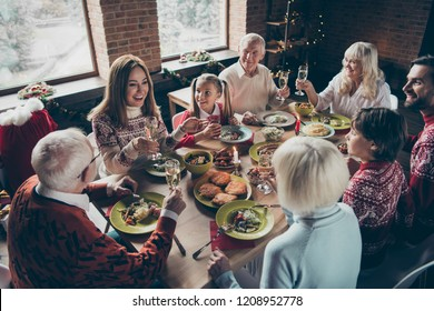 High above angle view of noel diverse family gathering. Cheerful glad grey-haired grandparents, grandchildren, brother, sister, sitting at table, fun joy house party, feast, tasty yummy food, clink