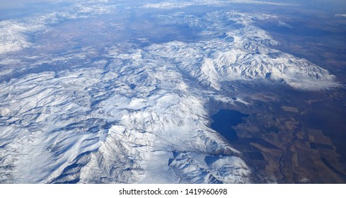 High above the snow covered Sierra Nevada Mountains as seen from an airplane in January.