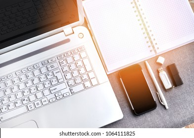 High above view of office workplace with mobile phone and laptop close up computer keyboard and mouse with notebook, pen and usb flash on grey desk. Working blogging desk table concept