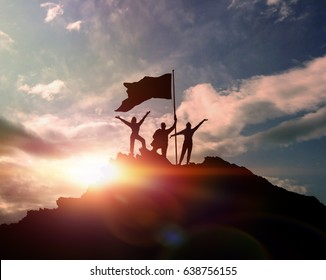 High achievement, silhouettes of three people holding a flag on the top of the mountain, hands up. A man on top of a mountain. Conceptual design. Against the dramatic sky with clouds at sunset.