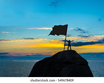 High achiever, silhouette of a man hold in hand empty flag on top of a mountain. Man on top of mountain. Conceptual design. male against blue and yellow dramatic sky with clouds. hand's up.