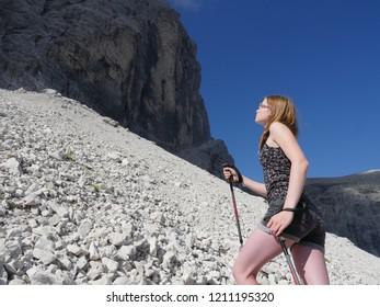 High Aims, Blue sky, Teenage girl hiking toward steep rockface on gravel