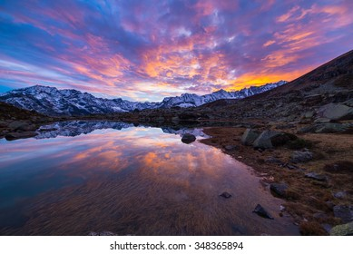 High altitude alpine lake in idyllic land once covered by glaciers. Reflection of snowcapped mountain range and scenic colorful sky at sunset. Wide angle shot taken on the Italian Alps at 2200 m asl.