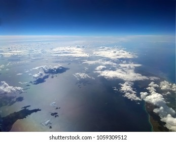high altitude image of the earth with blue sky and white clouds over the sea with sun reflected on the water and small islands
