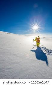 High altitude mountain explorer walking through deep snow in high mountains on a freezing winter day