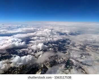 high altitude photograph of the snow covered alps with blue sky and white clouds covering the earth with curved horizon