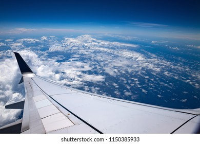 High altitude. Sky, clouds and atmosphere seen from an airplane. Ocean, white clouds, airplane wing and the earth atmosphere.