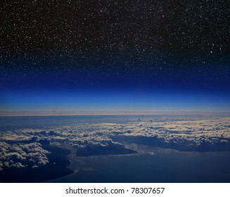 High altitude view of the Earth in space. Clouds follow the coastline and stars shine above.