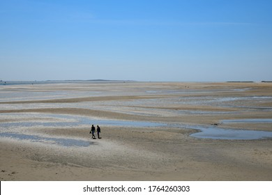 High angel panoramic view of the shoreline during low tide on Terschelling Island with tide pools and sand banks on a sunny and clear day, two people taking a walk on otherwise empty beach