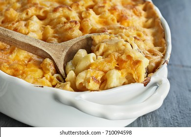 High angel view of a dish of fresh baked macaroni and cheese with a wooden spoon over a rustic dark background.