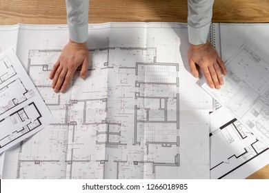 High angle above top view cropped smart professional lady in her formalwear shirt she stand at the table in bright loft interior put hand on desk look at document and new commercial project