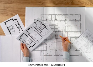 High angle above top view cropped photo clever intelligent success lady in her formal wear shirt she sit at the desk in bright loft interior hold graphs in hands read technical property information